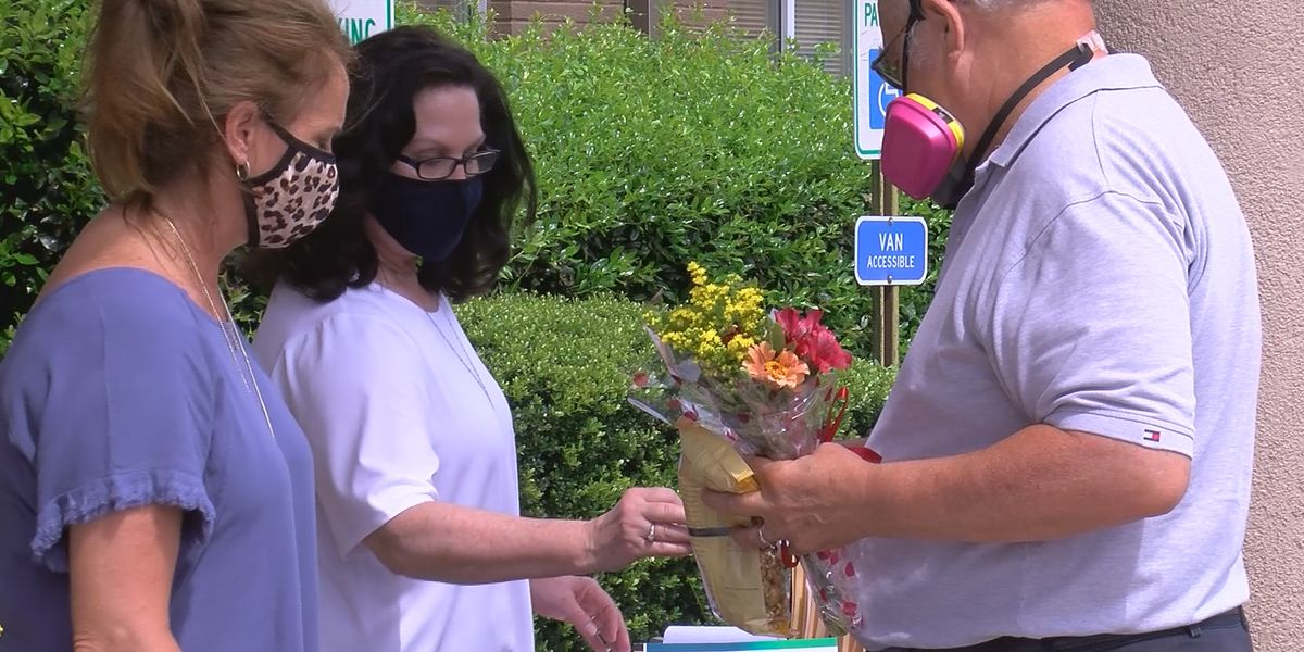 Volunteers show support with flower bouquets